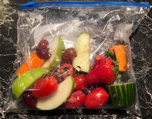 Oppskåret og skylt gulrot, eple, pære, stangselleri, agurk, cherrytomater, jordbær, sukkererter og druer