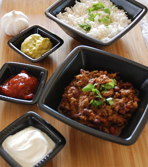 Chili con carne Ingredienser 1 Løk (liten) 1 Gulrot (liten) 1-2 fedd Hvitløk ¼ - ½ Chili (rød) 400 g Kjøttdeig 1 bx Tomater (hermetiske) 2 ts Persille (tørket) 1½ - 2 ts Spiskummin 1½ ts Koriander 2 ts Paprikapulver ½ ts Gurkemeie 1 ts Salt ¼ ts Pepper 300-400 g Bønner (Kidney, ferdig kokte)