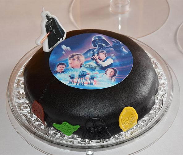 """Kaka består som sagt av tre kaker, satt opp på et kakestativ for bryllupskaker. Alle tre kakene har Star Wars tema. Den første kaka er en svart og har """"undertemaet"""": Darth Vader. Siden han er mørk består denne kaken av saftig sjokoladekake fylt med sjokolademousse. Syntes sjokoladekake passet godt til undertemaet. Som pynt på den svarte marsipanen er det et noen figurer fra Star Wars, et Darth Vader kakelys og et Star Wars kakebilde som skulle smelte ned i kaka, men som faktisk ikke gjorde det - så vi tok det vekk, når kaka ble sprettet."""
