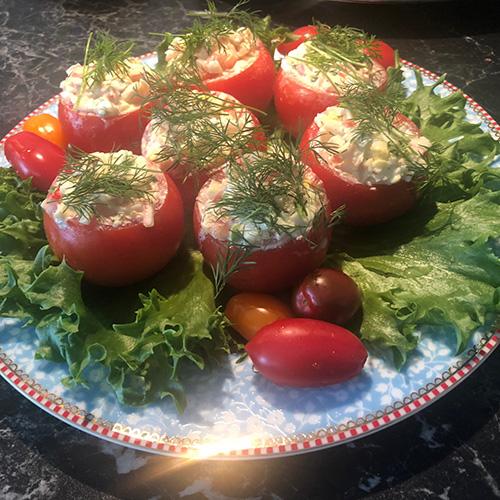Fylte tomater Ingredienser 6 Små harde tomater 1 Hardkokt egg 1 porsjon Crabsticks salat 1 Salatblad Cherrytomater, persille eller dill til pynt
