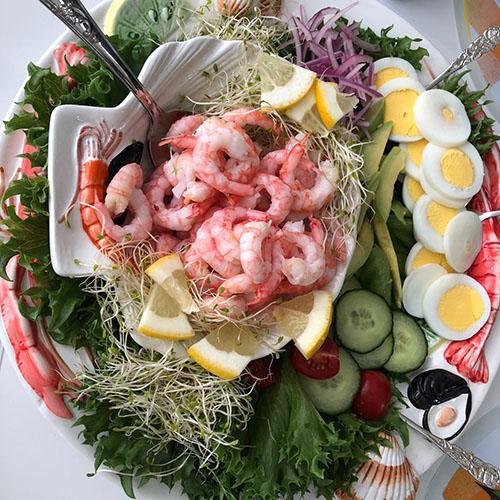 sommerlunsj med reker Ingredienser: 500 gr Reker (ferske) 1 Avokado 1/2 Agurk 1 pose Salat blad 10 Cherrytomater 1 Sitron 2 Egg (kokte) ½ Rødløk 1 Loff Smør, majones