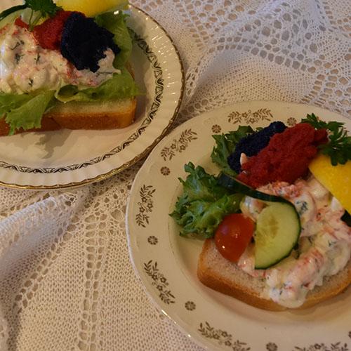 Ingrids Skagensrøre Ingredienser: 2 dl Rømme 2 ss Majones 1 ts Sennep ½ ts Søt chilisaus 2 ss Rødløk (finhakket) 2 ss Dill (finhakket) 2 ts Sitronskall (finraspet) 200 g Reker (renskede) 200 g Krepsehaler (renskede) Salt, pepper 4 Salatblader 4 ts Rogn ½ Sitron