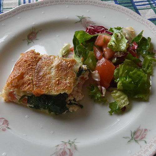 Spinat- og Ricottaterte med tomater Ingredienser: 300 g Butterdeigplater (dypfryste) 2 Tomater (tynne skiver) 1 pk Spinat 2 ss Smør 250 g Ricotta(ost) 100 g Hvit ost (revet) 3 ss Parmesan 10 blad Basilikum 1 Egg (sammenvispet) Salt, pepper 1 Eggeplomme 2 ss Parmesan (til strø)