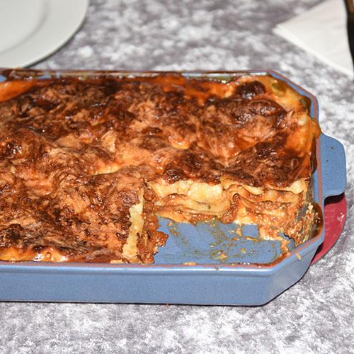 Lasagne al forno Ingredienser: Kjøttsaus: 2 ss Oliven olje 1 Løk 1 Gulrot 1 stilk Stangselleri 1 fedd Hvitløk ½ Chili (rød – uten frø) eller (kajennepepper) 350 g Kjøttdeig 50 g Bacon (kan sløyfes) 2 bx Hermetiske tomater 1 dl Vann (eller hvitvin) 1-2 Buljongterninger ½ - 1 ts Sukker Bladpersille (hakket) Salt og Pepper Ostesaus: 4 ss Hvetemel 8 dl Melk 1 ts Salt ½ ts Pepper 100-200 g Ost (revet)