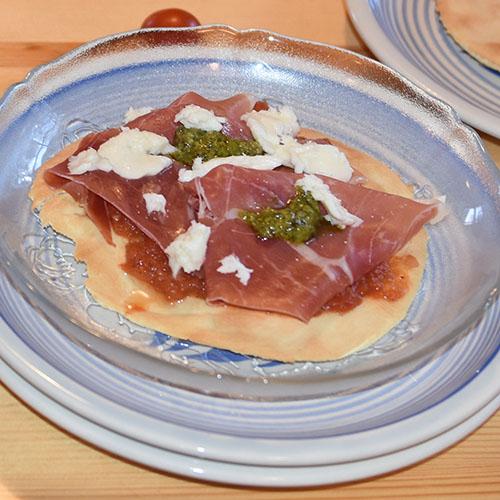 Pizzabunner etter oppskrift fra Baker Brun Ingredienser: Bunner: 4 dl Hvetemel 1 ½ dl Vann ½ pk Tørrgjær 1 ts Salt 3 ss Olivenolje Tomatsaus: 3 Sjalottløk (finhakket) 3 fedd Hvitløk (finhakket) 2 ss Olje (oliven) 2 bx Tomater (hermetiske) 1 dl Vann 2 ss Oregano (hakket, frisk) ½ ts Sukker 1 ts Salt