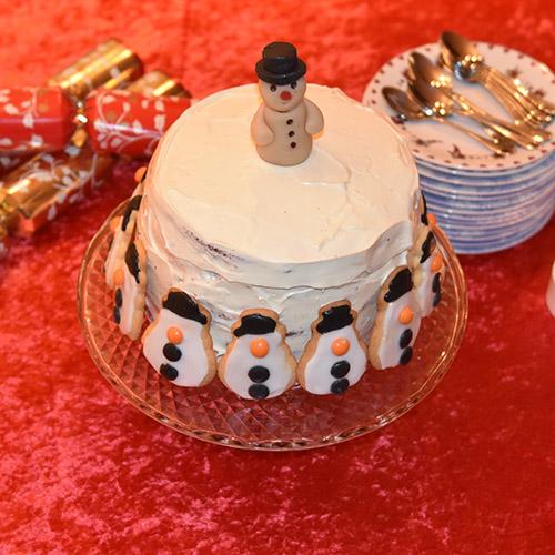 Snømannkake Ingredienser: 450 g Hvetemel (7 ½ dl) 400 g Sukker (5 dl) 4 ss Maisenna (70 g) 4-5 ss Kakao (70 g) 1 ss Natron 1 ts Bakepulver 4 Egg 3 dl Rømme 3 ½ dl Vann (varmt) 1 dl Olje (nøytral) 1 ts Vaniljeekstrakt 1 ts Eddik (eplesider) 2 ss Konditorfarge (rød) Fyll og topping: 500 g Kremost (Philadelphia) 225 g Smør 600 g Melis 1 ts Vaniljeekstrakt Pynt: Marsipansnømann Snømannkjeks