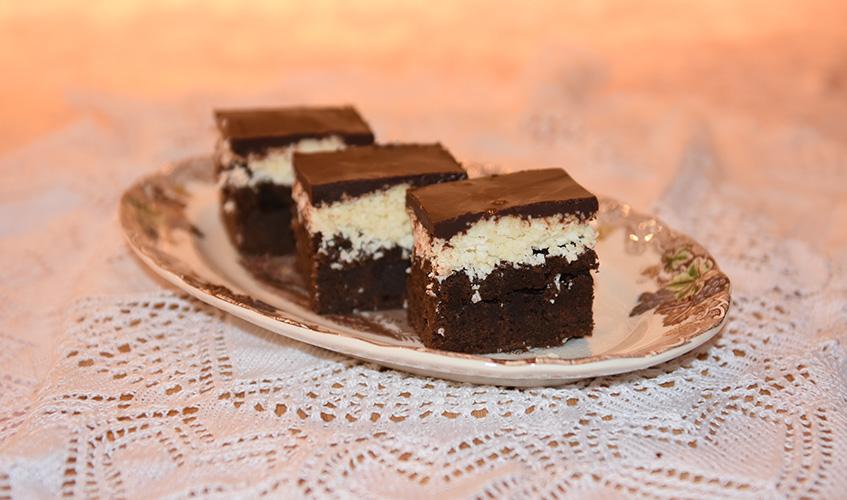 Brownies med kokos- og sjokoladetopping Ingredienser: 160 g Hvetemel 5 ss Kakao 225 g Smør 2 ts Kaffepulver 120 g Brunsukker 200 g Sukker (hvitt) 5 Egg 2 ts Vaniljesukker Kokostopping: 180 g Kondensertmelk (søt) 1 ts Vaniljesukker ¼ ts Salt 400 g Kokos 220 g Melis Sjokoladetopping: 220 g Sjokolade (mørk) 1 ts Sirup (hvit) eller glukose 115 g Smør