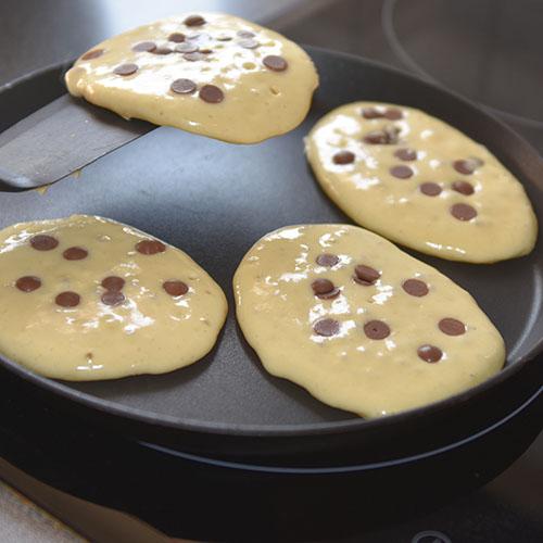 Amerikanske pannekaker med sjokoladebiter Ingredienser: 50 g Smør 2½ dl Melk 2 Egg 3 dl Hvetemel 2 ts Bakepulver ½ ts Salt 1 ss Sukker 100 g sjokoladebiter