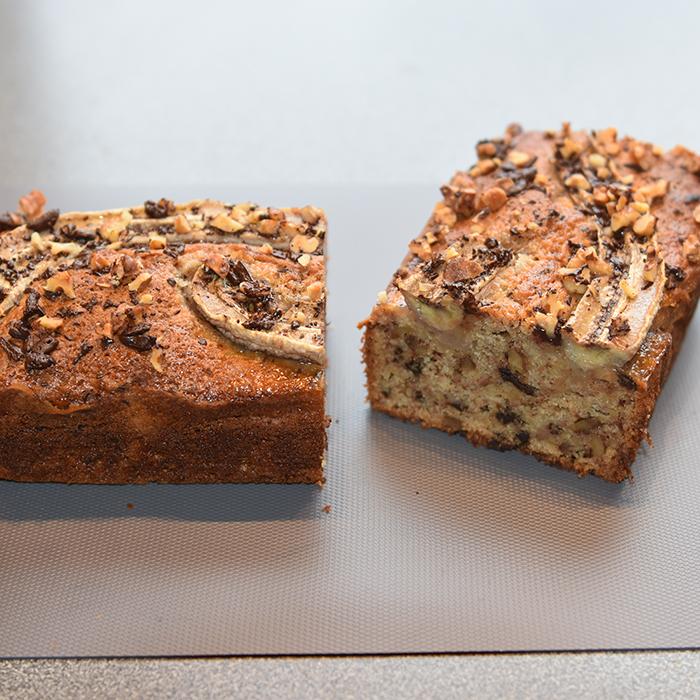 KRISTINS BANANBRØD Ingredienser: 2 ½ dl Hvetemel 2 ts Bakepulver 1 ts Vaniljesukker 1 ts Kardemomme (valgfritt) 2 Egg 1 ½ dl Sukker 50 g Smør 1 dl Melk 40 g Kokesjokolade (mørk, hakket) 40 g Valnøtter 2 Bananer (godt modne, gjerne med brune flekker) Topping: 10 g Kokesjokolade (mørk, hakket) 10 g Valnøtter 1 Banan
