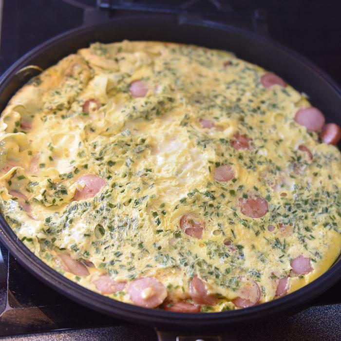 Pølseomelett Ingredienser: ½ - 1 ss Smør 3 Egg 3 ss Melk (eller vann) 2 Grillpølser 1 ss Gressløk (hakket) - valgfritt 1 ss Persille (hakket) - valgfritt Salt og pepper