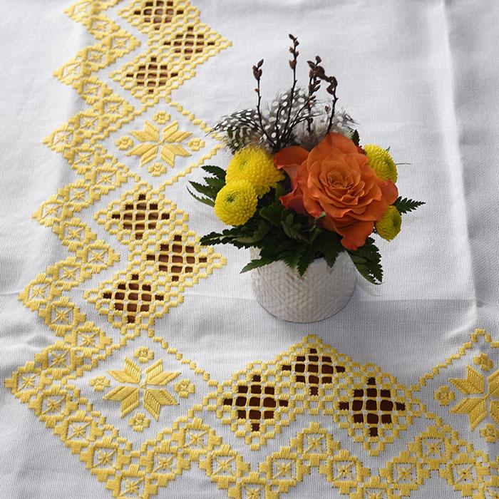 Liten Oppsats med gule og oransje blomster på gul påskeduk, sydd med Hardangersøm