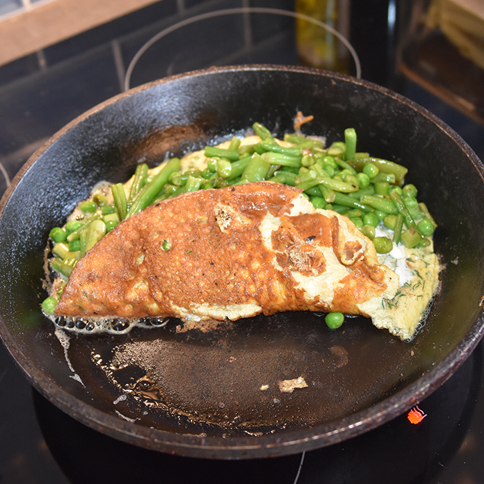 Grønn omelett Ingredienser: 200 -250 g Erter, sukkererter, aspargesbønner og asparges (skjært i mindre biter) 4 Egg Salt, pepper 4 ts Vann Dill og persille 4 ss Smør 2-3 ss Rømme (lett)