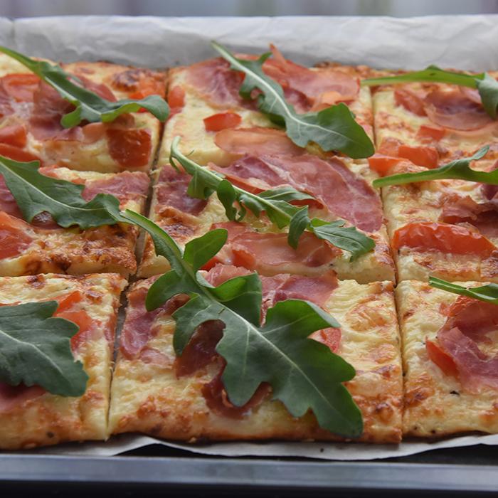 Hvit pizza med spekeskinke og ruccula  Ingredienser:  Pizzabaunn:  1 ssSukker 2 tsTørrgjær 2 dl Vann (ca 36 grader) 450 gHvetemel ½ ts Salt  3 ssOlje (oliven)  Tips! La deigen heve i kjøleskapet, da tar det ca. 8 timer. Dekk bollen med plast før du setter den inn.  Fyll og topping 1 bxRømme (gjerne lett) 2 fedd Hvitløk 150 gOst (hvit, raspet) 2 Tomater (skivet) 9 skiverSpekeskinke 1 pkRucculoa