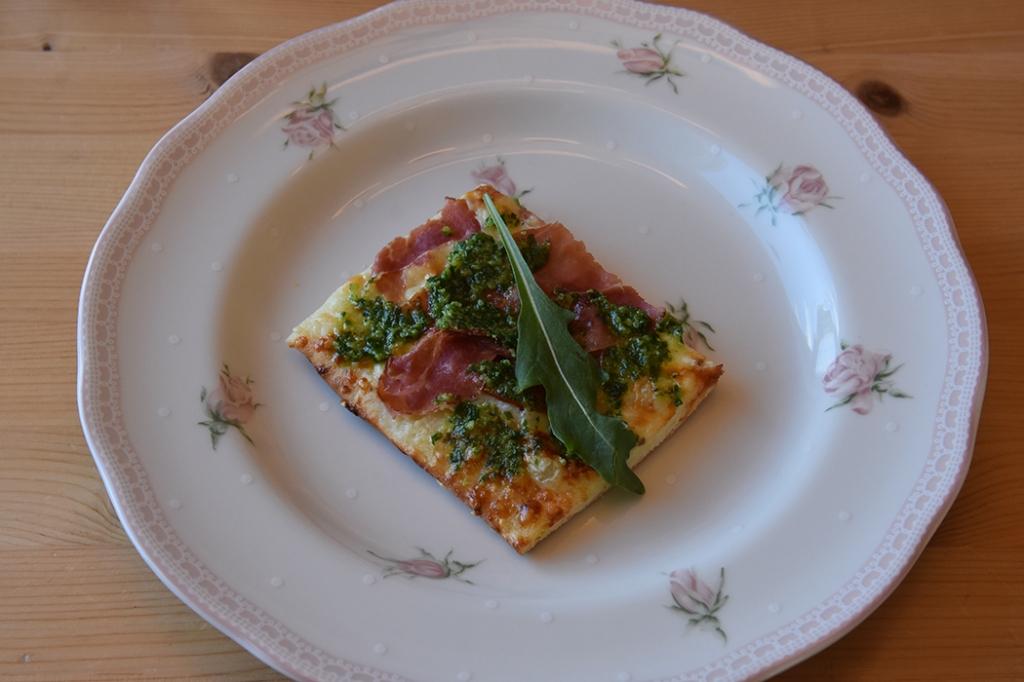 Hvit pizza med spekeskinke, ruccula og ramsløkpesto  Ingredienser:  Pizzabaunn:  1 ssSukker 2 tsTørrgjær 2 dl Vann (ca 36 grader) 450 gHvetemel ½ ts Salt  3 ssOlje (oliven)  Tips! La deigen heve i kjøleskapet, da tar det ca. 8 timer. Dekk bollen med plast før du setter den inn.  Fyll og topping 1 bxRømme (gjerne lett) 2 fedd Hvitløk 150 gOst (hvit, raspet) 2 Tomater (skivet) 9 skiverSpekeskinke 1 pkRucculoa   Ramsløkspesto:  400 gSpagetti 100 gRamsløk 1 feddHvitløk 3 - 4 ssParmesan (revet) 3 - 4 ssPinjekjerner 1 ¼ dlOlivenolje ¼ tsSalt Pepper (nykvernet)