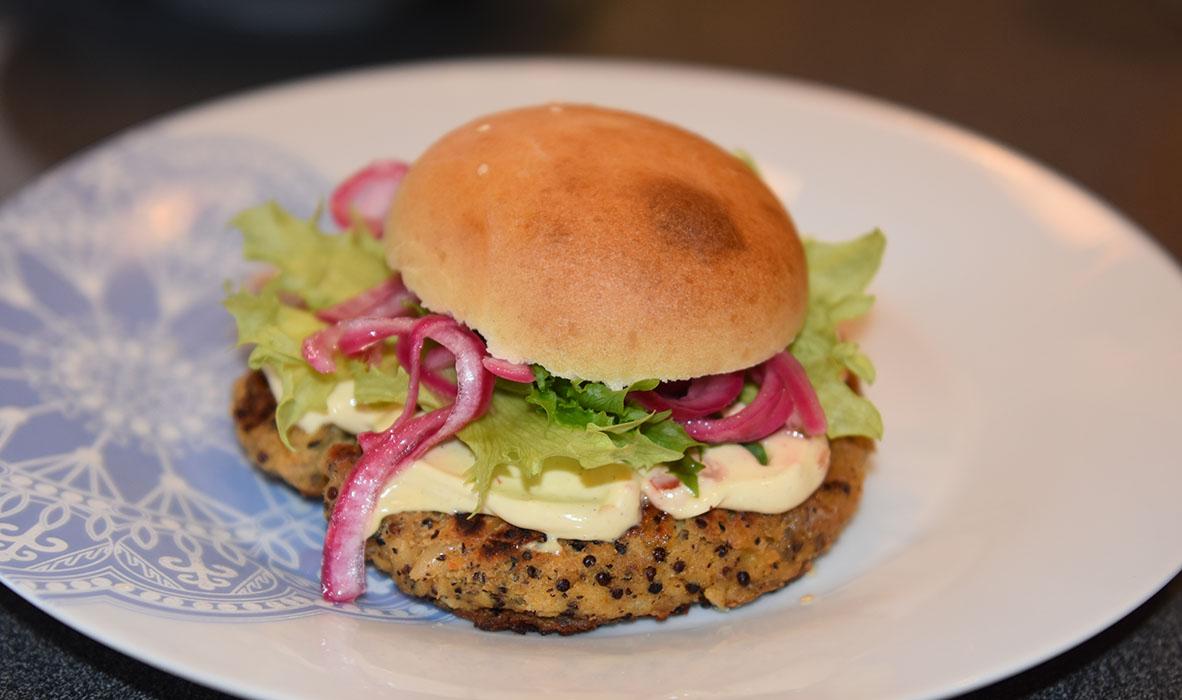 Quinoaburger Ingredienser: 50 g Quinoa 1 dl Grønsakskraft (eller -buljong) 400 g Bønner (hvite) 1 Sjalottløk ½ ts Kajennepepper 1 ts Paprikapulver 1 ss Oregano (tørket) 1 ts Koriander (malt) 1 ss Ketchup 30 g Brødrasp 1 Egg Salt, pepper Olje 4 Hamburgerbrød Salat