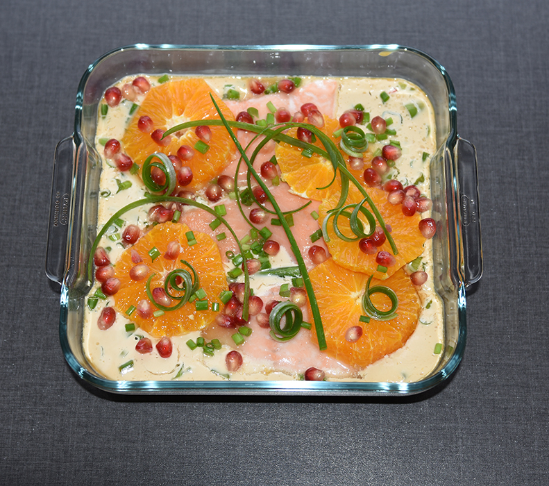 Laks i rømmesaus med appelsin og granateple Ingredienser: Ca. 400-500 g Laksefileter (uten skinn og bein) 1 bx Rømme 1 Appelsin (saft) ½ Sitron (saft) 1 ½ ss Honning 3 ss Soyasaus ¼ Chili (rød) 2 Vårløk Topping: 1 Appelsin (skivet) 1 Granateple (frø) Gressløk/vårløk