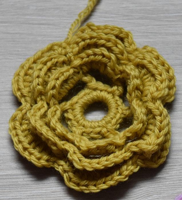 Heklet Rose Sik gjør du (Roser): Tvinn tråden 3-4 ganger rundt en finger og sett sammen med en kjedemaske (kjm) Omgang 1: 1 luftmaske (lm), 17 fastmasker i ringen, avslutt med 1 kjm i den 1. lm Omgang 2: 6 lm Hopp over 2 fm 1 halvstav (hst) i neste fm *4 lm Hopp over 2 fm, 1 hst i neste fm* GJENTA fra * til * 3 ganger til 4 lm Avslutt med 1 kjm 1 den 2. lm (på begynnelsen av omgangen) Omgang 3: I hver av de lm-buene hekles det: 1 fm, 1 hst, 3 st, 1 ht, 1 fm Avslutt med 1 kjm 1 den 1. lm (på begynnelsen av omgangen) Omgang 4: 1 kjm i bakre del av hst fra omg nr.2 *5 lm Hold garnet på baksiden av blomsten 1 kjm i neste Hst fra omg nr 2 * GJENTA fra * til * 4 ganger til 5 lm Avslutt med 1 kjm i den samme hst som i begynnelsen av omg Omgang 5: I hver av lm-buene hekles det: 1 fm, 1 hst, 5 st, 1 ht, 1 fm Avslutt med 1 kjm 1 den 1. lm (på begynnelsen av omgangen) Omgang 6: 1 kjm i bakre del av hst fra omg nr.4 *5 lm Hold garnet på baksiden av blomsten 1 kjm i neste Hst fra omg nr 4 * GJENTA fra * til * 4 ganger til 5 lm Avslutt med 1 kjm i den samme hst som i begynnelsen av omg Omgang 7: I hver av lm-buene hekles det: 1 fm, 1 hst, 7 st, 1 ht, 1 fm Avslutt med 1 kjm 1 den 1. lm (på begynnelsen av omgangen)