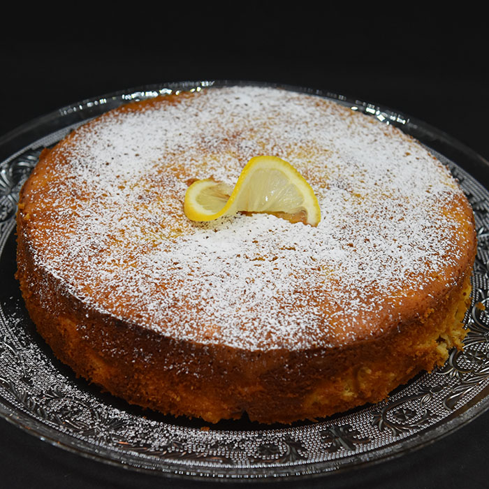Spenstig sitronkake med pærer og fersken Ingredienser: 125 g Smør (smeltet) 2 Pærer (godt modne) 2 Fersken (godt modne) 2 Sitroner (skall og saft) 4 Egg 2 dl Sukker 3 ½ dl Hvetemel 1 ts Bakepulver