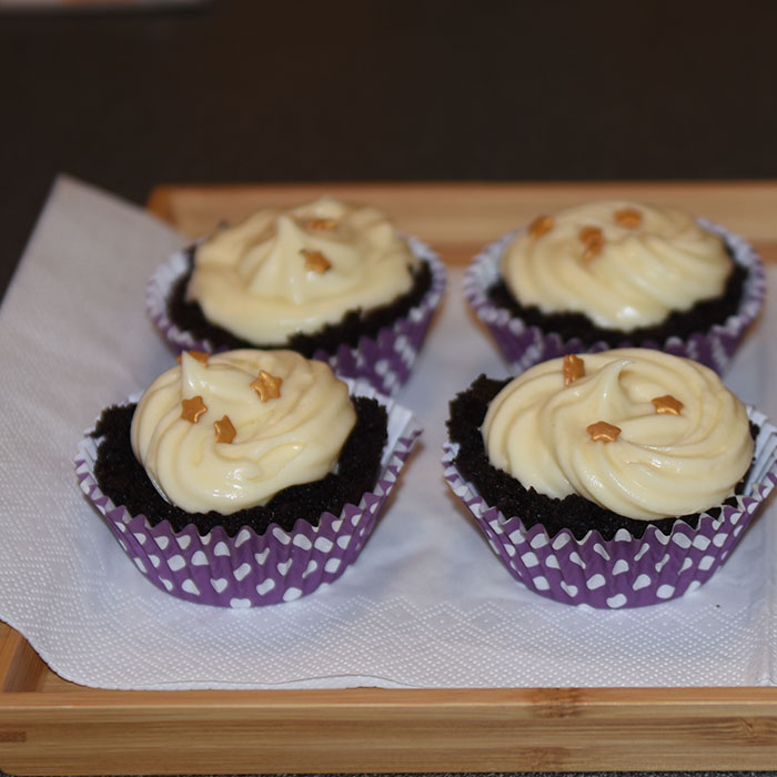 Mørke saftige sjokolademuffins med hvit sjokolade- og kremosttopping Ingredienser: 2 ½ Kaffe (varm og sterk) 2 ts Vaniljesukker 70 g Sjokolade (mørk) 2 Egg (romtempererte) 1 ¼ dl Olje (nøytral) 2 ½ Fløte 500 g Sukker 190 g Hvetemel 150 g Kakaopulver 1 ½ ts Natron ½ ts Bakepulver Hvit sjokoladeostekrem topping: 400 g Sjokolade (hvit) 350 g Smør (romtemperert) 200 g Melis 1 pk Philadelphiaost 1 ss Vaniljesukker 1 ss Limesaft (valgfritt)